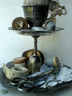 Tarnished silver tray holding vintage sewing goodies.