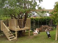 """Simple tree house built around the tree incorporating the tree asa """"roof"""". Like the swingset addition"""