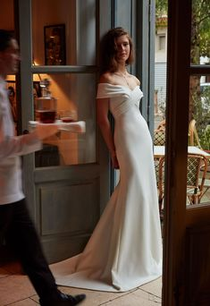 An off-the-shoulder sweetheart neckline gives this stunning ivory crepe gown an elegant, feminine air. Details like the criss-crossed bodice and sweeping train make it unforgettable.