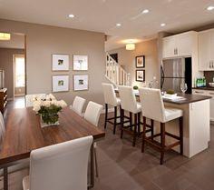 white kitchen, stainless appliances, dark countertops, white railing
