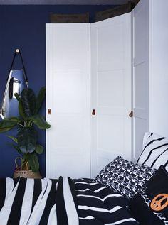 A white corner wardrobe in a blue bedroom.