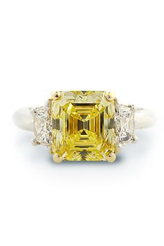 Platinum size 6.5 ring featuring .41ctw G/VVS Trapezoid side stones & a center 2.75ct FIY/IF GIA Emerald cut Diamond set in 18k yellow gold. Available at Oster Jewelers.