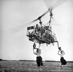 """""""K190"""" helicopter attempting a three-point landing atop the heads of three women holding plywood squares as landing """"pads,"""" 1948."""