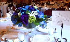 Clear glass compote vase with a textured mound of blue hydrangea, purple lisianthus, anemone, white nerine lilies and bright green viburnum for u of m wedding reception guest tables