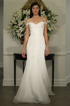 This gown of point d'esprit lace features a scallop sweetheart neckline with a draped off-the-shoulder silk organza detail and a softly fluted skirt made of silk organza. Note: This is a sample dress from a Nearly Newlywed 'preferred boutique partner.'
