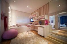 O quarto da pré-adolescente tem detalhes delicados como o pufe rosa, adornos com patchwork, mas ao mesmo tempo conta com detalhes modernos e irreverentes como a cadeira em acrílico e o papel de parede em listras verticais coloridas http://ow.ly/blPso