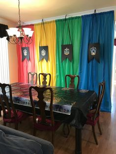 "Colored plastic tablecloths made a colorful (and inexpensive) addition to the ""Great Hall"" for my son's party! I used painters tape to ""gather"" the tablecloths before hanging them. The signs are made with black poster board and house patches printed on my color printer."