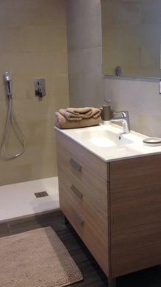 Baño pequeño con ducha y inodoro suspendido