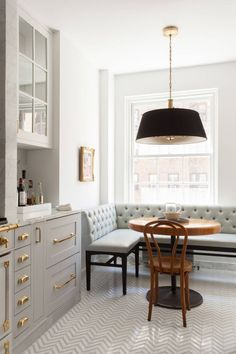 Gray cabinets, brass hardware, Carrara marble, tufted banquet seating, herringbone flooring—so much to love in this NYC kitchen!