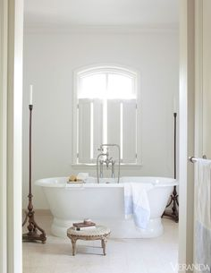 A pale palette and storied antiques surround this bath tub. Limestone in the master bath was cut like plank wood flooring. Bathtub, Van Dyke's Restorers. Fittings, Waterworks. Image originally appeared in the May/June 2012 issue of Veranda.  INTERIOR DESIGN BY DARRYL CARTER   - Veranda.com
