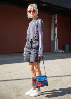 Que tal usar short no seu look de trabalho? Se inspire nesse visual com camisa listrada, shorts cinzas, tênis branco e bolsa colorida.