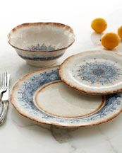 bursts of blue on this dinnerware were Vista Del Sol - painted by hand—the intricate pattern resembles lace dotted with orange accents.