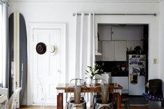 Kristin Barone, gray and white striped surfboard, white curtain hides kitchen, metal tolix stools, via Remodelista
