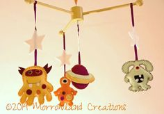 Aliens From Planet Tlef Mobile perfect for babies and children.  The Planet Tlef is a fantastic place where Jelly grows on trees. It's not a big planet with just 5000 inhabitants. You can't get up to much mischief without someone you know finding out! Read more about this planet and the aliens who live there at www.morrowlandcreations.co.uk #NurseryDecor #BabyMobile #ABabyShower