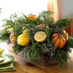 Replace fruit with blooms     Freshen with Botanicals  --  Elevate a humble wooden box to Christmas-centerpiece status. Start by lining the box with dry florist's foam to anchor evergreen sprigs. Attach citrus fruits (lemons, oranges, limes) to florist's picks and tuck into the greenery. Add interest by cutting some of the fruits in half or adding decorative details.