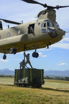 U.S. Army Spcs. Jack Wood and David Swain, assigned to the Army Forces Battalion, attach a container to a CH-47 Chinook during air load and fly-away training on Soto Cano Air Base, Honduras, Nov. 25, 2014. The cargo was delivered to the U. S. Southern Command Situational Assessment Team at the Warrior Ramp for employment in the day's training event.