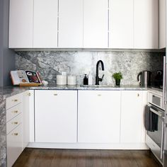 The white flat cabinets and minimal brass handles on the lower cabinets only make the kitchen ultra modern with a touch of glam. The silvery grey veined countertop that run up the wall as backsplash add elegance and class and instantly make the kitchen look high-end.