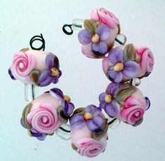 "Pink and lavender, so pretty together.  Includes: 6 floral rounds approximately 11 mm from hole to hole.    Beads were wound on a 3/32"" mandrel and kiln annealed for strength and durability."