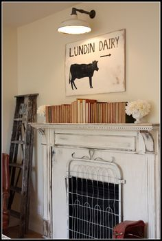 Love the way salvage was used here: the ladder, the mantle, the old fence piece as a grate and love the light above the fireplace!