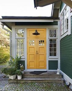 Green, white and a bright yellow double front door! Charming and fresh entry, front door, porch, and a brick path or walkway to the BEST colors! Yellow Front Doors, Double Front Doors, White Doors, Cottage Front Doors, Swedish Cottage, Swedish House, Cottage Style, Swedish Style, Exterior Paint