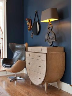 The indigo walls in this living space highlight the unique shape of the leather  chair and curved design of the side table. | summer design
