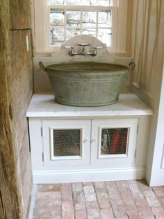 My sink in my outdoor kitchen must be like this!! I like the chicken wire on doors and the brick floor also.