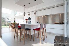 Une cuisine design italien total look blanc avec îlot central, finition laque blanc brillant pour le mobilier et Quartz Glacier white pour les plan de travail.