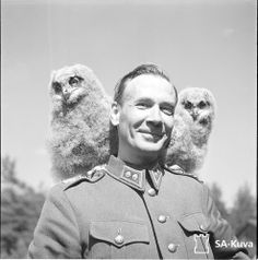 Two Eurasian eagle owl chicks sitting on shoulders of lieutenant colonel Laaksonen 1941 (x-post from r/Suomi)