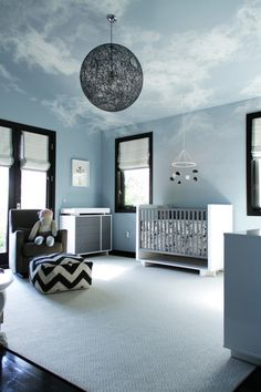 Pokój dla dziecka i jego niesamowita dekoracja. Niebieski kolor został zestawiony z czarnym kolorem stolarki okien i czarnymi elementami wyposażenia wnętrza. Świetna iluzja chmur na suficie, bardzo realna i spokojna. Zainspiruj się!