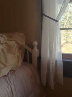 Shabby chic makeover bedroom. Sheer curtains are very elegant and pretty against tan walls and mahogany window
