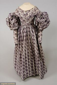 PURPLE PRINTED MATERNITY DRESS, 1828-1835 November, 2007 -Tasha Tudor Historic Costume Collection White cotton ground printed with abstract red, green and purple floral print with stepped undulations forming stripes, high rounded neckline, center front brass hook & eye opening for nursing, center back closure with shell buttons, gigot sleeve cartridge pleated to piped armhole, narrow cuff with etched shell button, muslin bodice lining and hem facing, (minor stains in lining) excellent.