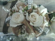 rose/gold corsage with peach/cream roses and white wax flower.