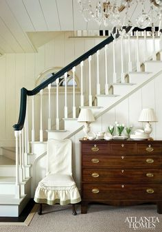 white plank ceilings & walls, black and white banister, chandelier