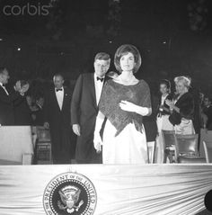 """President and Mrs. Kennedy Original caption: 11/29/1962-Washington, DC- President and Mrs. Kennedy are shown as they film a nationwide closed circuit television show, """"An American Pageant of the Arts,"""" to boost a National Culture Center. Here, Mrs. Kennedy is shown in front of President Kennedy in the National Guard Armory. Date Photographed:November 29, 1962.❤✽❤✽❤ http://en.wikipedia.org/wiki/Jacqueline_Kennedy_Onassis  http://en.wikipedia.org/wiki/John_F._Kennedy"""