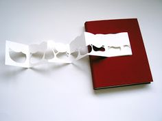 A private commission, this rounded spine cloth bound book contains many different types of paper, pockets and fold out pages. The cover is inlayed with a hand cut paper tree that can be removed and displayed separately...by Sarah Mitchell.