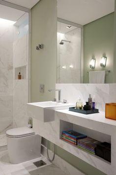 Com a redução do quarto de hóspedes, nasceu o novo banheiro que também serve a ala social da casa. A bancada esculpida em mármore piguês abriga a louça e tem nicho para guardar revistas. O boxe vai de piso a teto delimitando as áreas do ambiente
