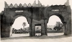 Nigeria, view of Bauchi gate. Double arched gate through what appears to be a city wall. Trees and circular, thatched-roof buildings visible through gate. Medium: Gelatin silver print.