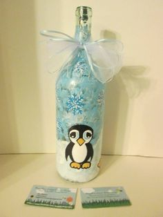 Penguin Winter Wonderland lighted wine bottle(white lights) with white tulle and blue ribbon at the top! View #4. https://www.facebook.com/buggybeandesigns