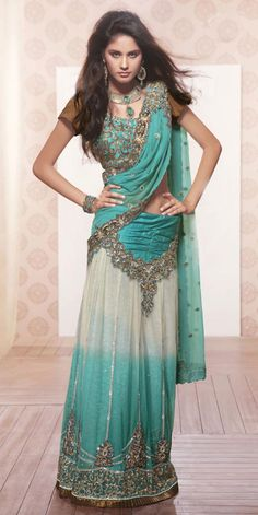 Eye-popping cream and turquoise color net kalidar lehenga saree with fantastic patch border is prettified with shimmering sequins, jari, stones, resham embroidered floral motifs, stylish gathered yoke part and frill patch border on bottom of skirt part are increasing its beauty with charm. The sensuous party wear looks are perfect for every personality.