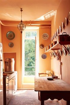 Traditional Orange Kitchen in the eighteenth-century French country home of textiles dealer Susan Deliss - deep in rural Burgundy with traditional colourful interiors.