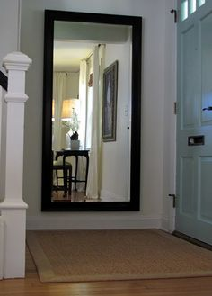 Mirror at the landing of the stairs. Love the light blue front door.