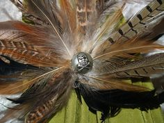 Large Feather Hair Fascinator. We us an alligator hair clip with teeth for securing to your hair or to your head band or attach to hat band. Super grip for fine hair or short hair. Assortment of feathers including phesant feathers and other feathers.    Featuring a skull pirate type medallion. On...