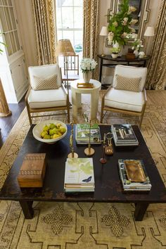 Conversation Pieces - Idea House Living Room by Mark D. Sikes - Southernliving. The neat stacks of books give guests plenty of options to perusewithout feeling like they have to walk around the room. The pop of color from the fresh pears also breathelife into the space.