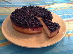 Cheesecake met bosbessengelei en verse blauwe bessen.