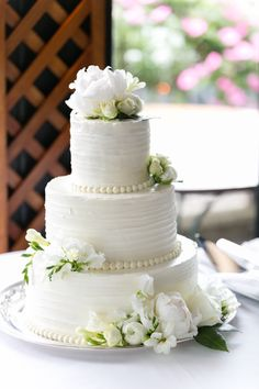 Three tier pearl wrapped flower topped wedding cake: http://www.stylemepretty.com/new-york-weddings/new-york-city/brooklyn/2016/10/24/mimosas-marriage-this-brooklyn-brunch-wedding/ Photography: Emilia Jane - http://emiliajanephotography.com/