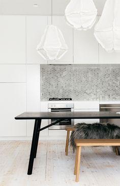 white kitchen cabinets + black table + silvery mosaic b/s + bench + white paper pendants