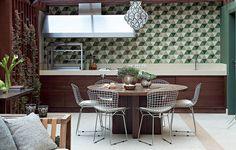"""""""A ideia era ter um espaço para cozinhar sem abrir mão do verde"""", conta a arquiteta Flavia Gerab. Desenhados pela profissional especialmente para este projeto, os ladrilhos hidráulicos hexagonais têm a função de integrar visualmente varanda e jardim"""