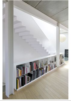 white girders/support beams & bookcase as railing under the stairs
