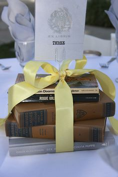 Book centerpieces. Find nice vintage books or add pretty covers to less elderly ones. Ribbons without bows. Set little candles or vase of feathers on top