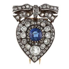 This vintage-style brooch showcases a large round-cut blue sapphire center stone surrounded by old mine-cut white diamonds in a heart and bow design. Crafted of silver and gold, this estate jewelry of